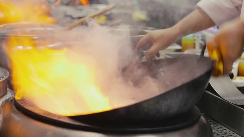 Asian restaurant with chinese chef cooking food, man as professional cook working, stir frying and preparing sauteed vegetables in pot on flame, fire, stove. 26of27