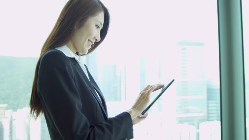 Female Asian Chinese female business executive standing window modern skyscraper overlooking city using tablet head shoulders shot on RED EPIC | Shutterstock HD Video #6374129