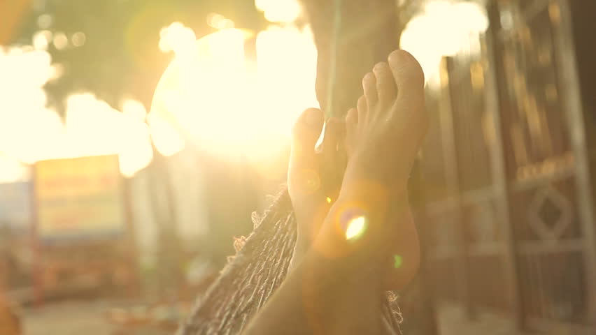 Feet swinging in a hammock, POV. Relaxing on the beach at sunset with flare.  | Shutterstock HD Video #6380339