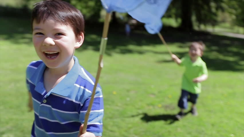 Little Asian Boys Run Happily Through A Field With Their Butterfly Nets. Asian family playing outdoors.