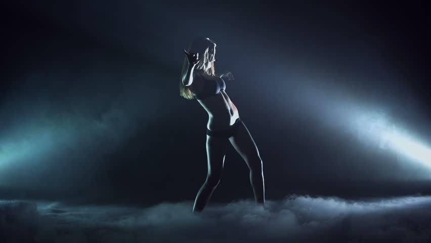 Attractive girl dancing in the dark in slow motion, spotlight at her side