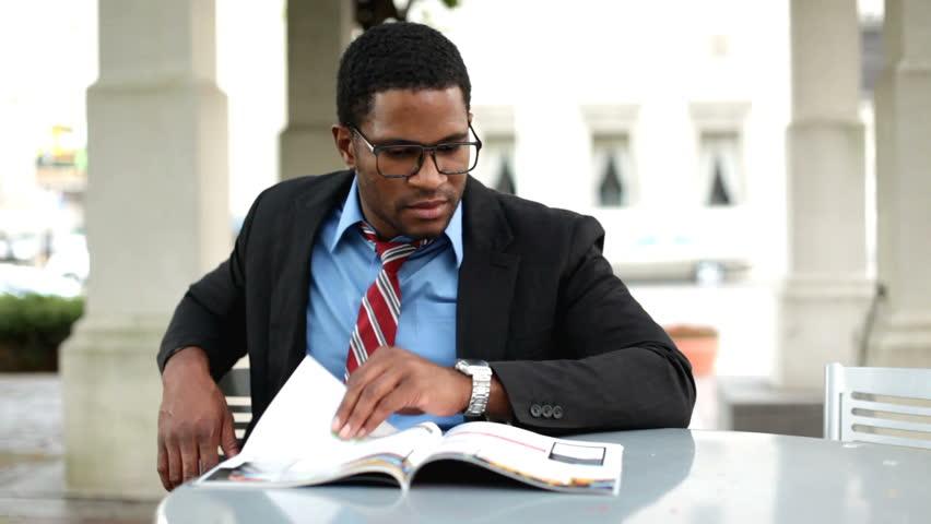 Business man reading magazine outdoors