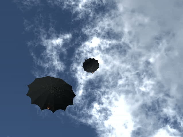 Two black umbrella's float down from a rich blue sky with white puffy clouds then across a green grass field. Original Animation