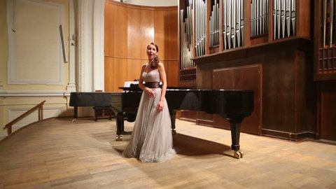 Opera stage with graceful woman pianist playing piano and singer