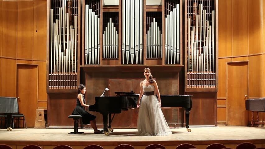 Woman pianist plays the piano and singer emotionally sing opera song at stage