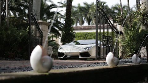 Cinematic Lamborghini driving through mansion gates slider shot