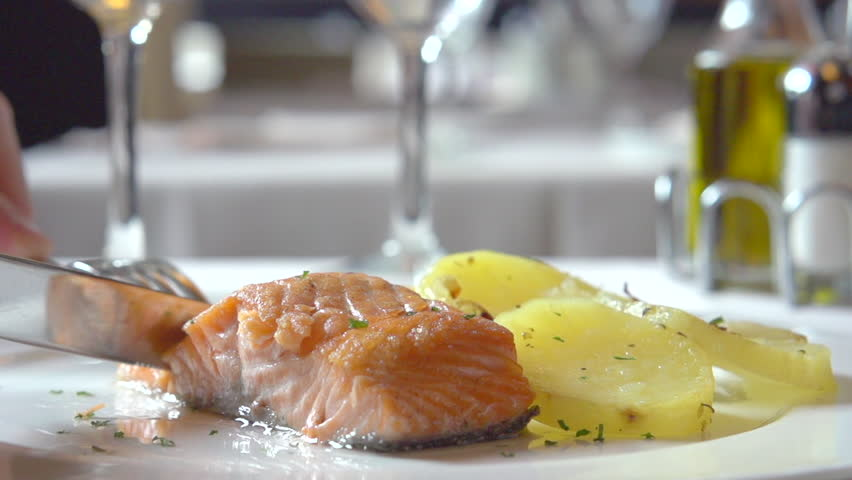 Person eating in restaurant. Salmon fish steak with potato. Dinner in a restaurant. Seafood. Serving table, plate, dish. Healthy food. Main course Close up. Slow motion video footage. Slowmo. Slow-mo