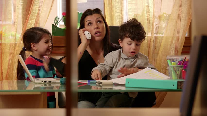 Multitasking mom working at home with children, busy with daughter and son, talking on telephone. Woman, family stress, parenting, motherhood. Businesswoman, manager at work in office, telework. 7of15 | Shutterstock HD Video #6431369