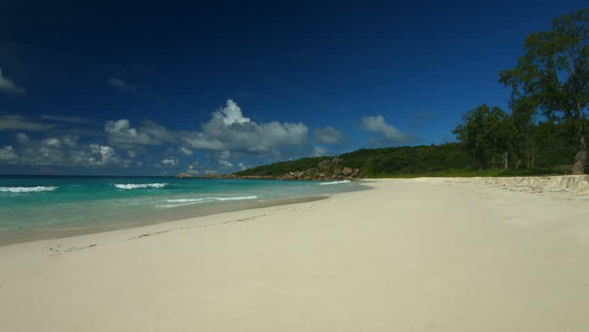 4K beach footage, waves arriving on wide sandy beach of tropical island