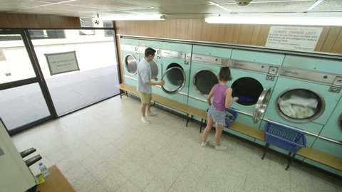 Three Young Adults do their laundry in the Launderette