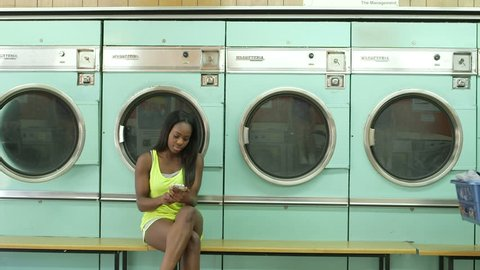 A Young Woman and a Young Woman meet in a Launderette whilst doing their laundry