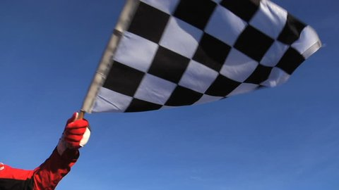 Race official waving checkered flag. Shot at full speed.