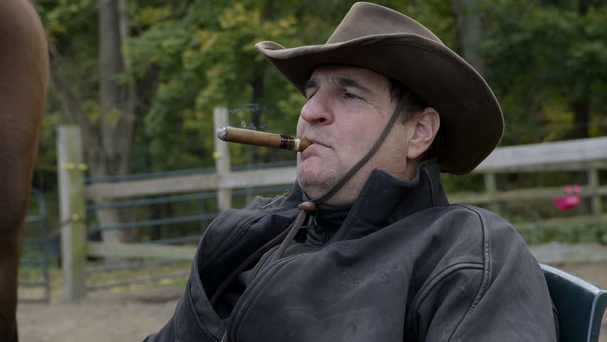 Close up of a cowboy smoking a cigar in slow motion