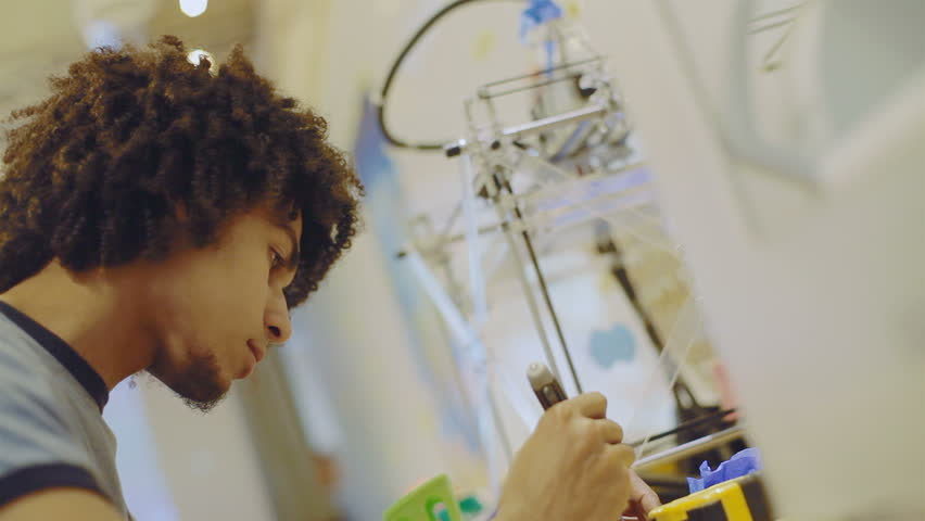 Young, creative young man experimenting with appliances and electronics