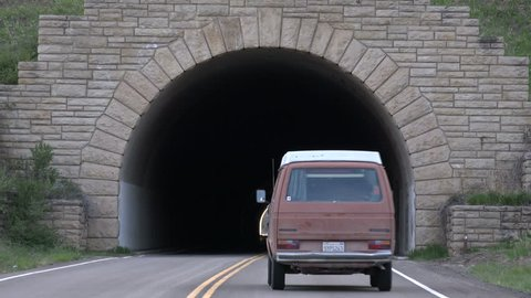 CORTEZ, COLORADO - MAY 2014: Long round tunnel through the mountains in Mesa Verde National Park. Old hippy VW bus vehicle. Ancient American Indian ruins. Historic Anasazi Pueblo cities and homes.