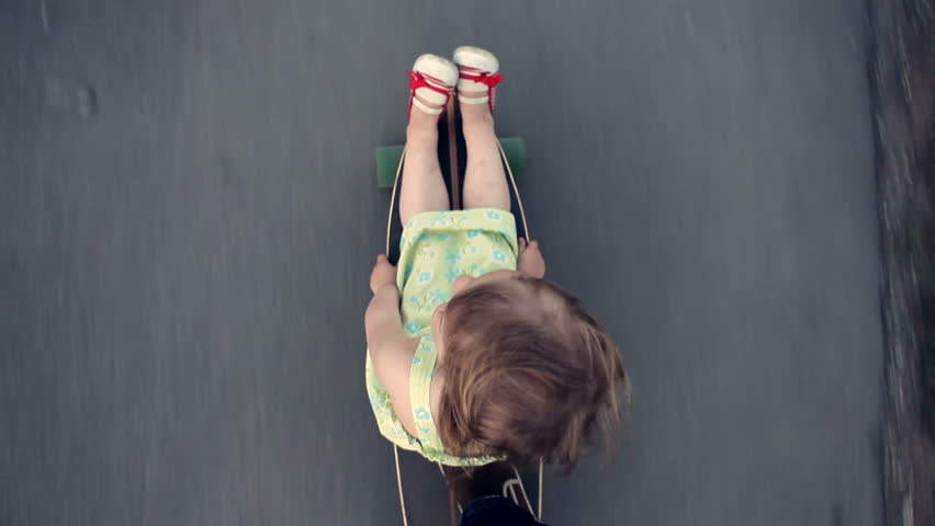 Little girl sits on a longboard, which is run by her dad. View from above. | Shutterstock HD Video #6482549