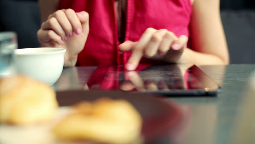 female hands working with tablet in the cafe