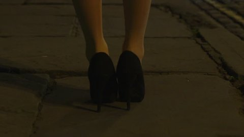 Young beautiful girl walking up an old cobbled street in a city on a cold winters night, camera pans up from her high heels to reveal her full length from behind. HD footage in slow motion