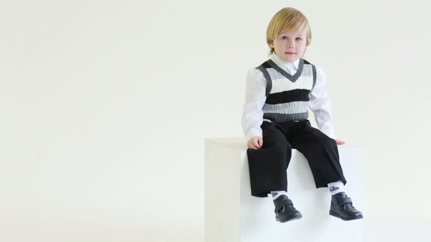 Little blond boy in vest sits on big cube, smiles and dangle feet
