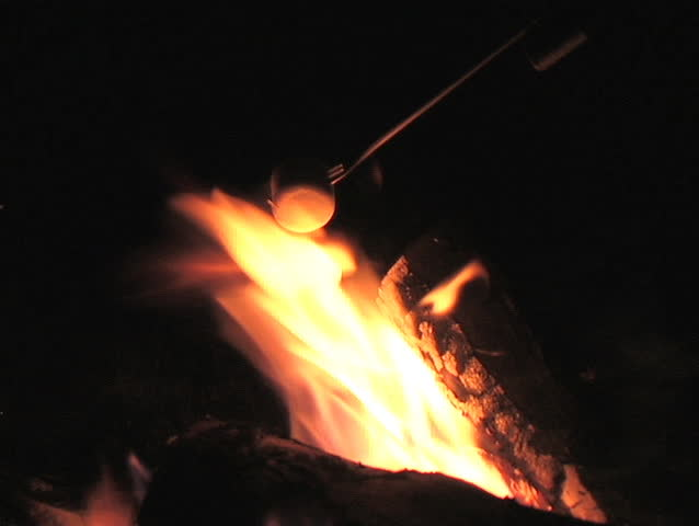 CLOSE-UP OF ROASTING A MARSHMALLOW OVER A FIRE