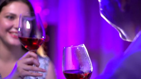 Young Couple Toasting Wine Glass In Restaurant. Dating. Young man and woman on romantic dinner drinking at restaurant, celebrating valentine day. Slow motion video 1080 full hd. High speed camera shot