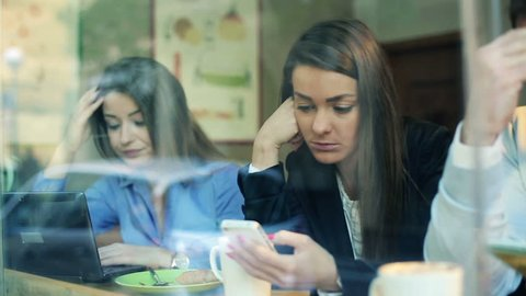 Worried business people checking bad news on electronic devices in cafe