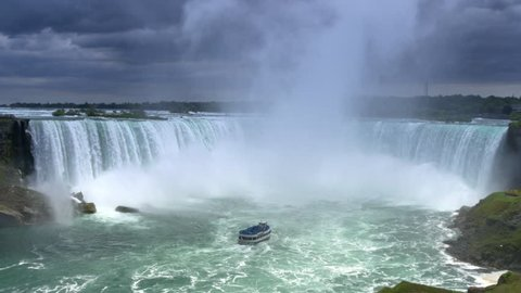 An establishing shot of the Horseshoe Falls on a summer day as the Maid of the Mist approaches below.