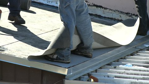 Roofers installing the final layer of membrane using hot bitumen on a flat roof