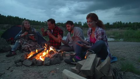 Pan of four people seated on ground eating by campfire and chatting