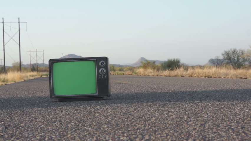 Dolly shot of a retro TV with a green screen in the middle of a road. | Shutterstock HD Video #6619019
