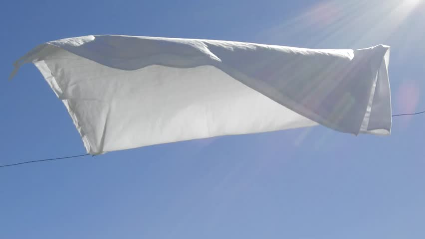 White sheet drying by a sunny and windy day