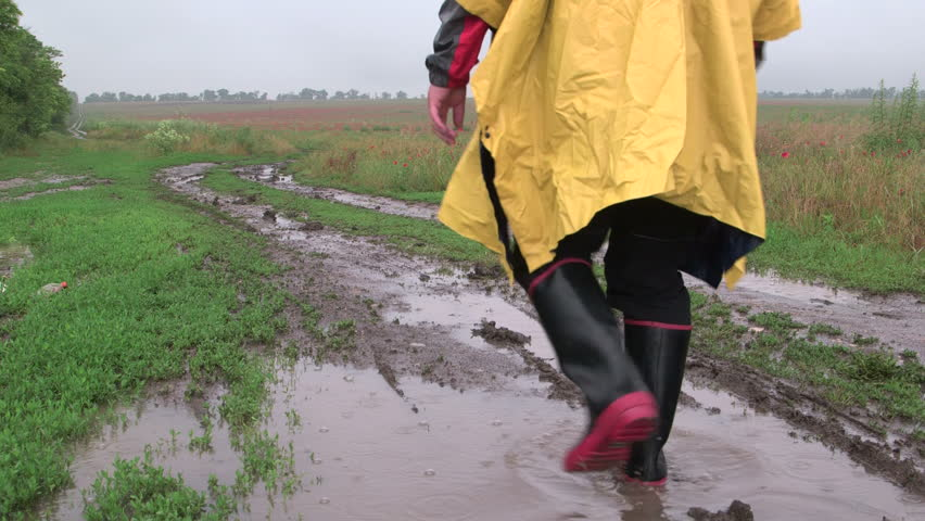 Man wearing yellow raincoat goes on a dirt country road through the field in rain