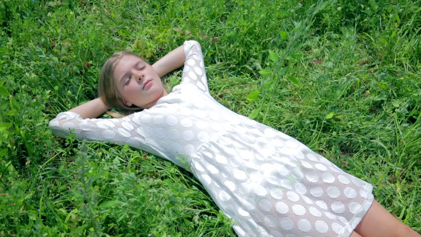 Girl In White Dress Laying In Grass Waking Up Stock -3167