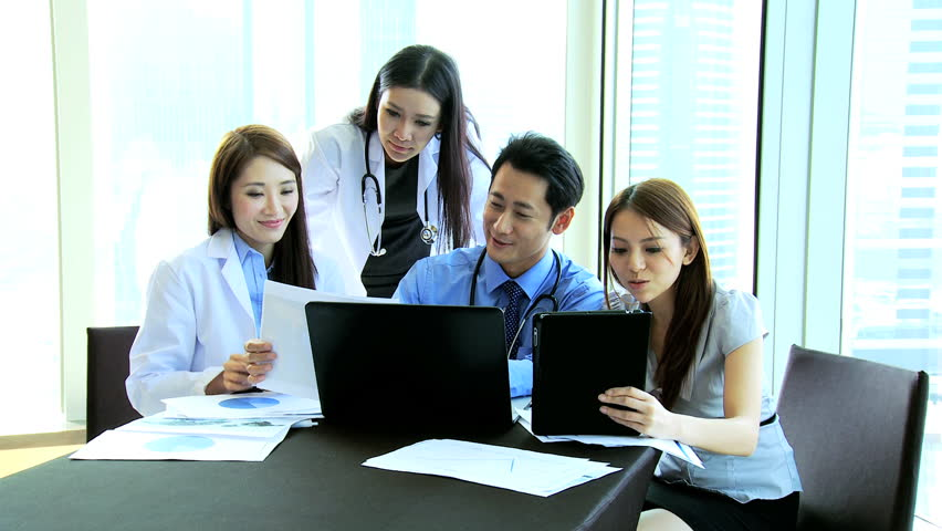 Confident young ethnic male female medical consultants wearing white coats using wireless tablet laptop collaborating hospital managers on future plans | Shutterstock HD Video #6643619