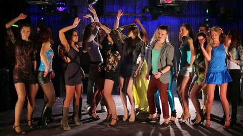 Eighteen happy young people dance and have fun at night club