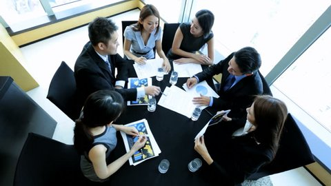 Overhead view ambitious male female Asian Chinese business team discussing ideas future contract bidding