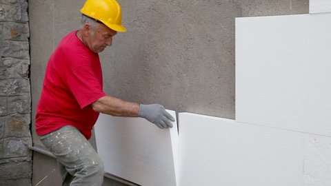 Worker placing styrofoam, polystyren sheet insulation to wall at construction site