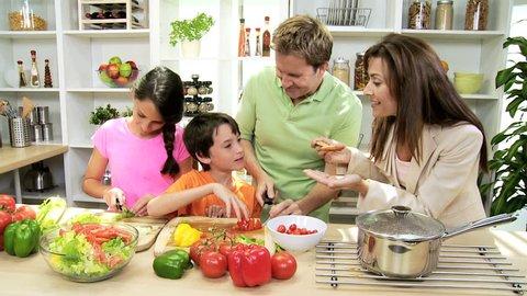 Professional Caucasian Family Group Preparing Dinner Together - Caucasian professional mom wearing business suit home kitchen husband children preparing healthy living dinner organic salad vegetables