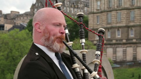 EDINBURGH, SCOTLAND - JUNE 03, 2014: Unidentified Scotsman with ginger beard plays the bagpipes. Scotland is famous for bagpipe music.
