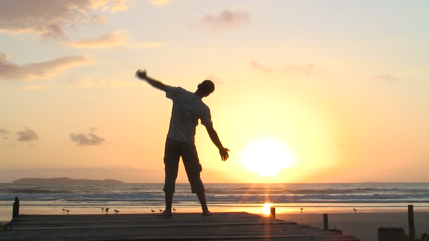 HD 1080i: Man doing relaxation exercises on a beach at sunrise.