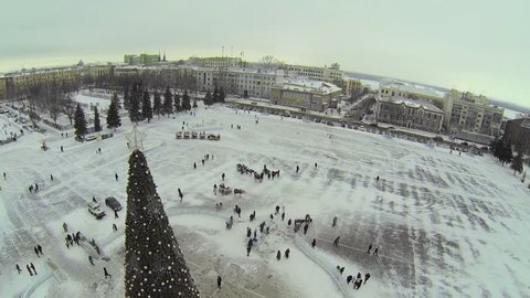 RUSSIA, SAMARA - JAN 6, 2014: Christmas tree on Kuibyshev Square with crowd near horsed carriages and small train for kids at winter day. Aerial view