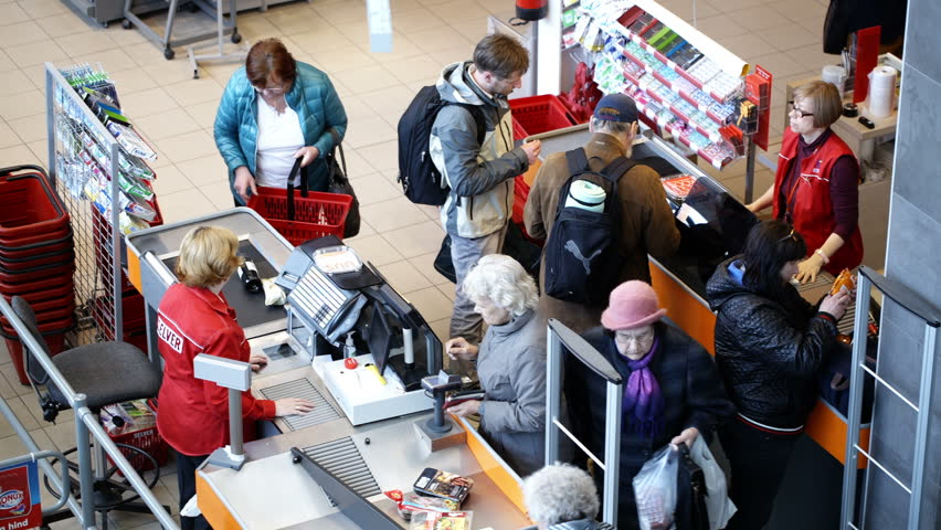 TALLIN, ESTONIA - MAY 24, 2014: Entrance and exit in the supermarket Selver. Some people coming in, some customer paying at the cashdesk or waiting in line. Focus on young man with product in hands