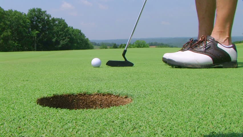 Close-up of golfer using putter to sink short putt into hole, with shotgun audio.