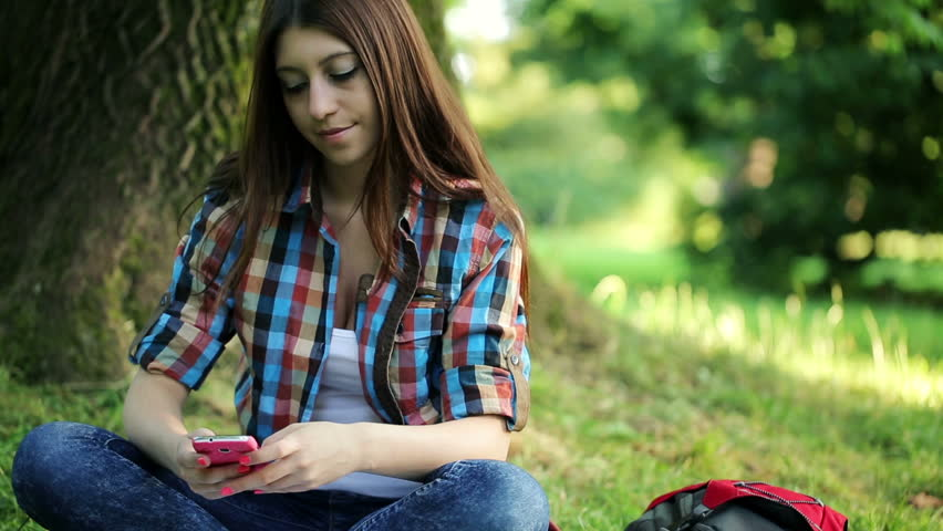 Young female student texting, sending sms on smartphone in the park