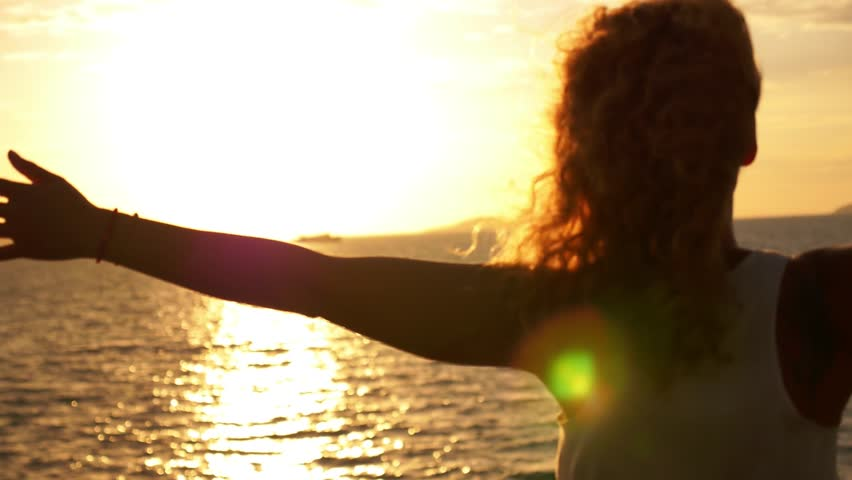 Young Happy Girl with Curly Hair and Tatto Spreading Arms at Beautiful Sunset. Sailing on the Ferry. Motivating Inspiring Slow Motion Video.