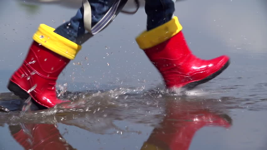 Low angled tracking shot of baby feet stepping in the pool in slow motion