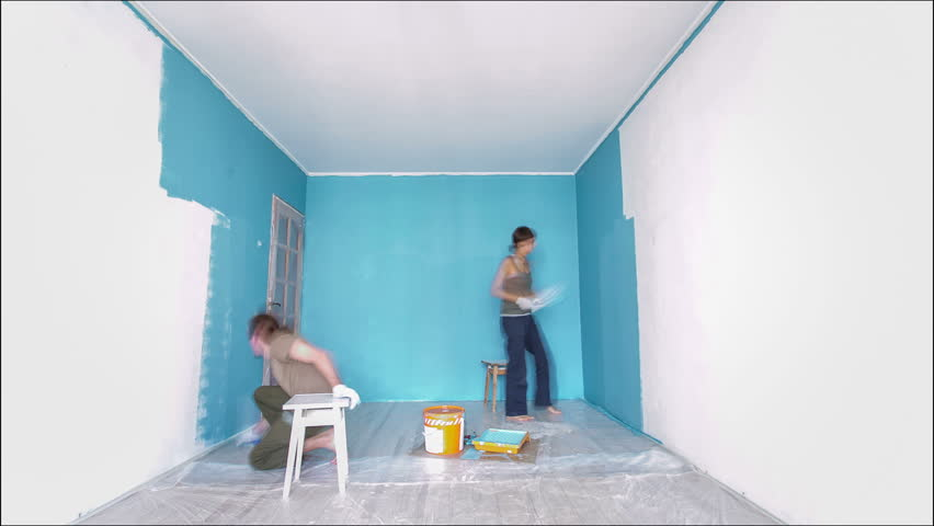 Time lapse Young couple painting wall blue at home