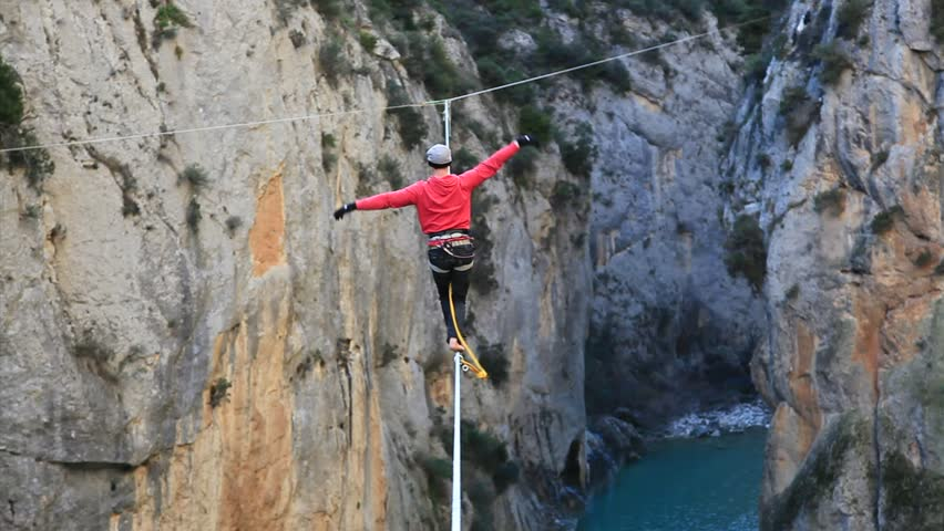 France, 2013. A man tightrope walking over high canyon, trying to keep his balance, starts to swing and falls and hangs from the rope
