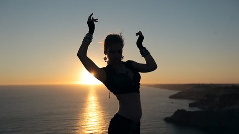 Amazing girl dancing belly dance at sunset near the sea