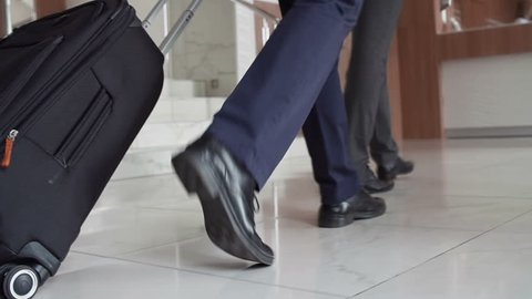 Low angled tracking shot of male feet with luggage coming up to the reception desk, tilted up so that faces are seen